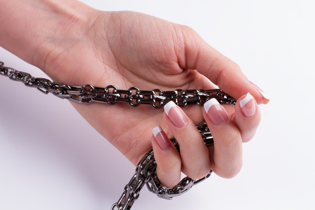 Chain in a female hand. Hand with a beautiful French manicure. Stock Photo