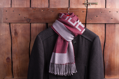 Winter mens coat with a warm scarf. Mens clothes hanging on a wooden fence.