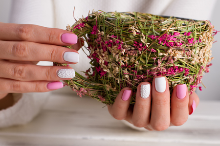 Work of art. Girl with a nice manicure holding a cup of hay.