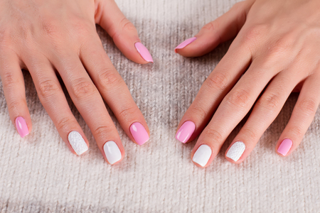 Well-groomed female nails. Female hands on knitted background.