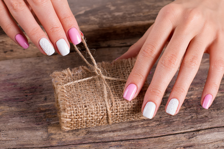 unleash: Womens hands with a nice manicure unleash a gift. Present in sackcloth on the old wooden background.