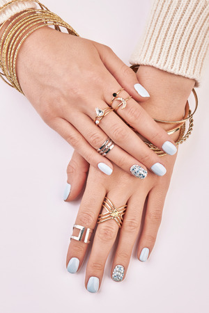 womens hands: Gold and silver jewelry on womens hands. Female hands with manicure on a white background.