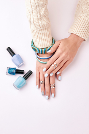 Silver rings and blue bracelets on womens hands. Beautiful nail polishes for manicure. Fashionable female manicure.