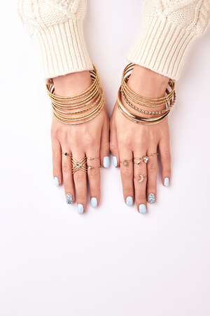 Many different bracelets and rings on hands. Hands with manicure on a white background.