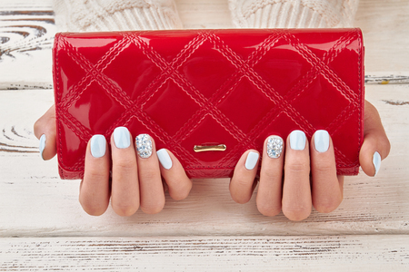Close-up of a red female purse in well-groomed female hands with a manicure. Red clutch and blue manicure.
