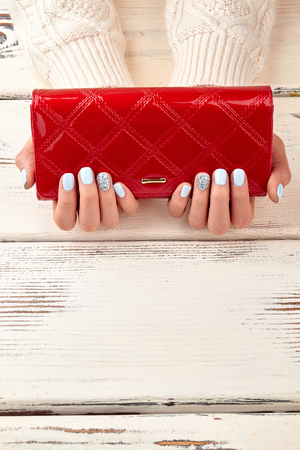 Red female purse in well-groomed female hands with a manicure. Red clutch and blue manicure on wooden background. Space for text.