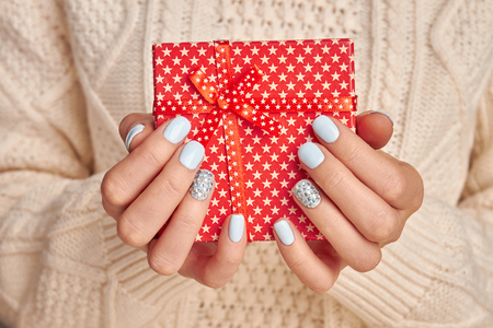 Beautiful little red gift with a star print. Beautiful female hands with a gentle blue manicure hold a gift.