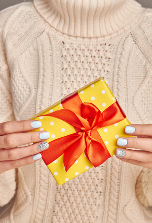womens hands: Beautiful yellow gift with a red bow against a knitted sweater background. Gift in womens hands. Stock Photo