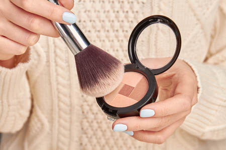 Brush with powder in female hands. Beautiful womens cosmetics. Cosmetics for everyday make-up.