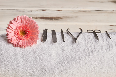 Beautiful pink gerbera with tools for manicure and pedicure. Detail of the interior of the beauty salon.