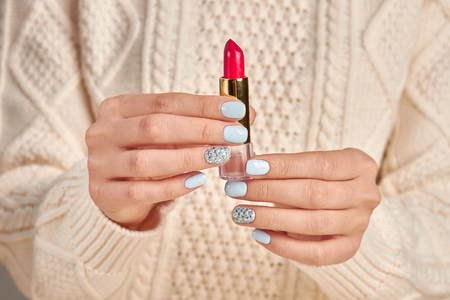 Woman's hand holds a bright red lipstick on an white sweater background. Trend blue manicure with red lipstick. Stock Photo - 82958139