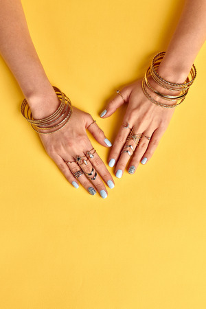 Beautiful summer gold bijouterie on female hands. Womens hands with a blue manicure on a yellow background.