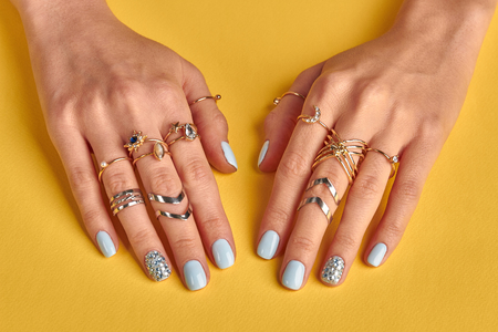Female hands with manicure closeup. Many beautiful gold rings on female fingers. Jewelry and blue manicure with rhinestones. Beauty salon. Stock Photo - 82958324