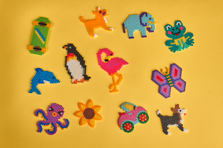 Many bright kids figures made of beads. Handmade toys for children. Funny toys.
