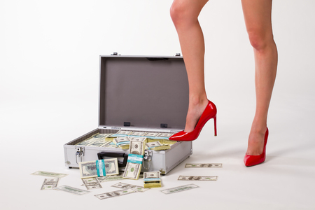Successful business woman. Suitcase full of dollars. Girl in red shoes.