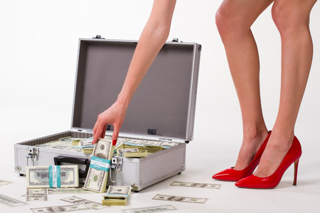 money packs: Sexy business woman. Suitcase with dollars. Girl in red shoes.