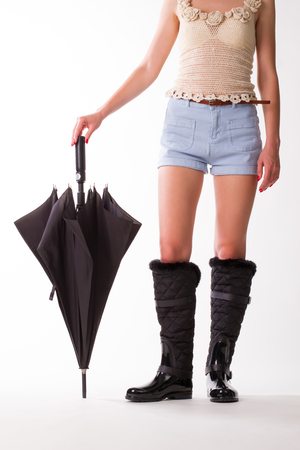 shorts t shirt sexy: Girl in black rubber boots and umbrella standing on a white background. Fashionable girl. Stock Photo