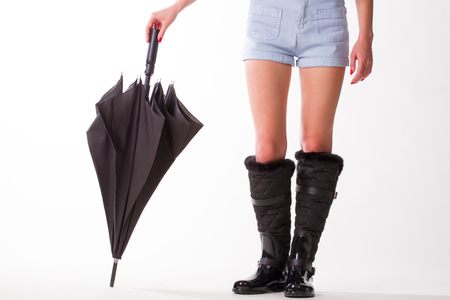 Woman in rubber boots and  black umbrella standing on a white background.