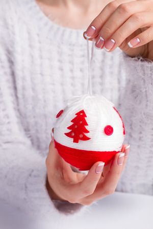 Girl in a beautiful fluffy sweater holding a Christmas ball. Well-groomed female hands holding a red ball on a rope. Stock fotó