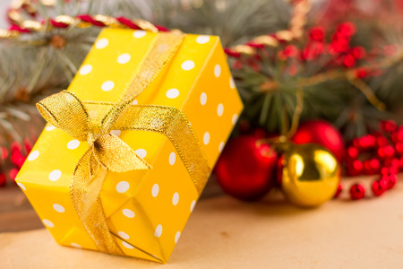 Beautiful yellow gift on the background of Christmas decorations. Christmas gift packaged in bright wrapper.