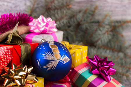 Beautiful blue ball with a candle on a pile of gifts. Preparing for the New Year. Gifts packed in colorful paper and shiny bows.