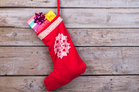 Red christmas sock with snowflakes for Santa gifts hanging on wooden background. Holidays symbol stocking.