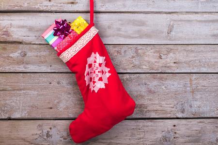 Rote Weihnachtssocke mit Schneeflocken für Sankt-Geschenke, die am hölzernen Hintergrund hängen. Feiertage Symbolstrumpf. Standard-Bild