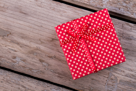 Red gift box with a star print on the old background. Small gift box with a pretty bow.