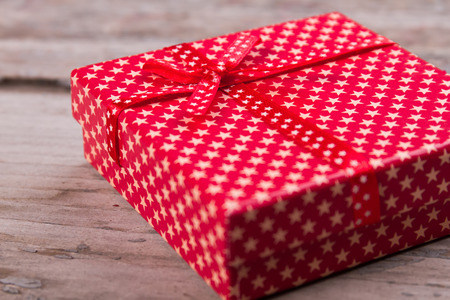 Beautiful gift box with stars print close up. Red box with a bow in the small stars.