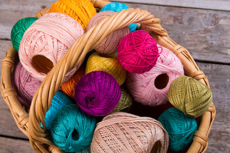 Many multi-colored threads for embroidery and yarn in a wicker basket.