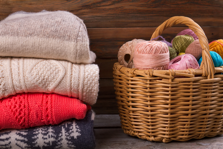 Stack of knitted sweaters on wooden background. Yarn in a wicker basket. Multi-colored threads for knitting.