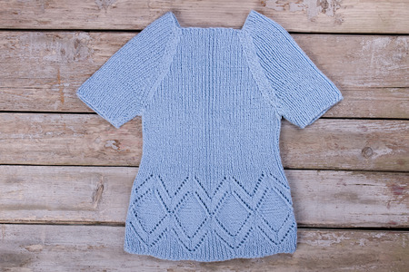 Beautiful blue handmade sweater. Knitted sweater on old wooden boards.
