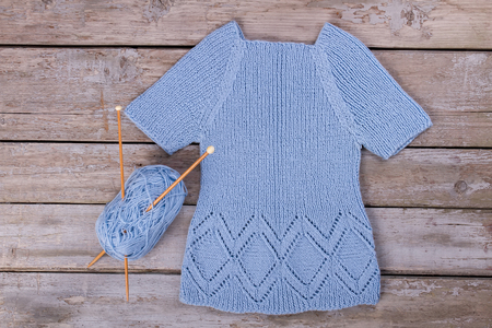 Knitted blue handmade sweater. Jersey with blue yarn and wooden knitting needles.