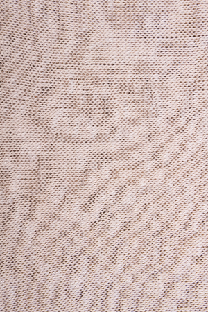 Beige knitted fabric texture. Knitted background. Natural fabric, sweater fragment. Detailed warm yarn background.