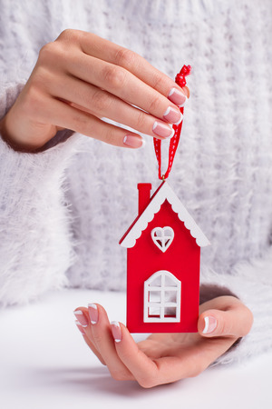 Beautiful Christmas toy. Red house in female hands.