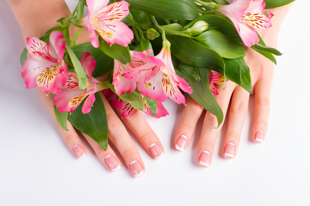 arm bouquet: Stylish lunar french manicure on a background of freesia flowers.