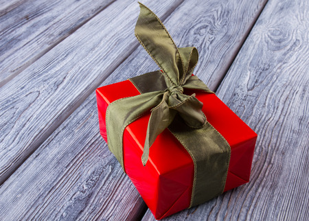Christmas gift on wooden table. Box wrapped in red paper and tied with satin ribbon. Time to give presents. Stock Photo