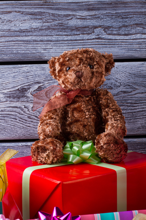 Teddy bear on gift box. Felt toys and presents for Christmas party. Winter holidays and celebrations.