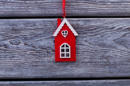 회색 나무 테이블에 리본으로 하우스 입상. 빨간색과 흰색 합판 장식 크리스마스 트리에 매달려.