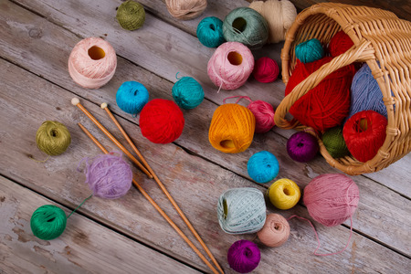 Colorful yarn spools and knitting needles on wooden background. Wicker basket for storing supplies. All for crochet.