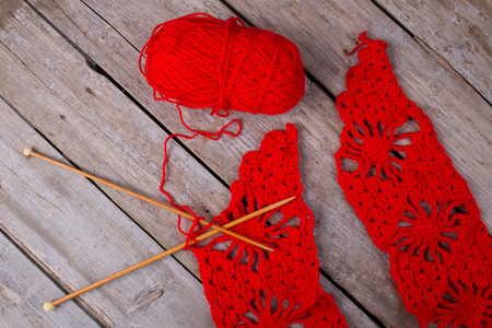 Making of red scarf. Bright red woolen yarn and wooden needles on rustic background. Knitting and crochet blog.