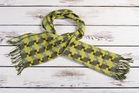 Beautiful green scarf on a wooden background. Warm bright winter scarf.