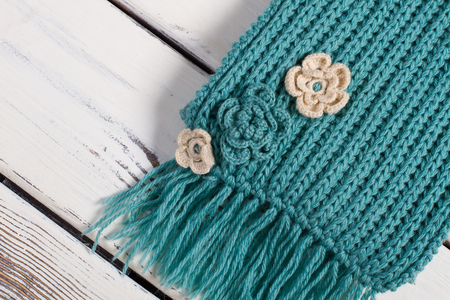 Detail of handmade knitted scarf.Wool scarf on a wooden background. Stock Photo