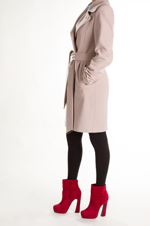 Stylish womens clothing. Girl in a beige coat and red ankle boots. Stock Photo