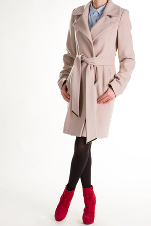 Girl in a beige coat and red ankle boots. Fashionable womens clothing. Stock Photo