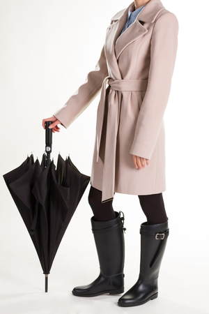 Girl in rubber boots and umbrella. Stylish woman on a white background. Stock Photo