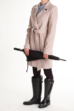 Girl in rubber boots with umbrella. Stylish woman on a white background.