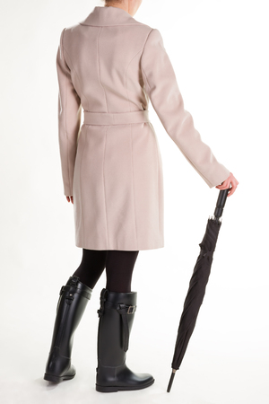 Autumn womens outfit. Fashionable girl in rubber boots with an umbrella.
