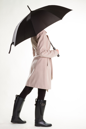 Girl in rubber boots and umbrella. Girl under the rain. Stock Photo