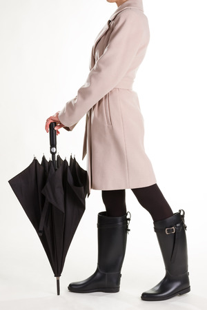 Autumn womens outfit. Fashion girl in rubber boots with an umbrella.